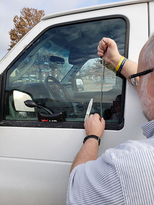 image of Chris unlocking the door of a van after the owner had locked their keys inside